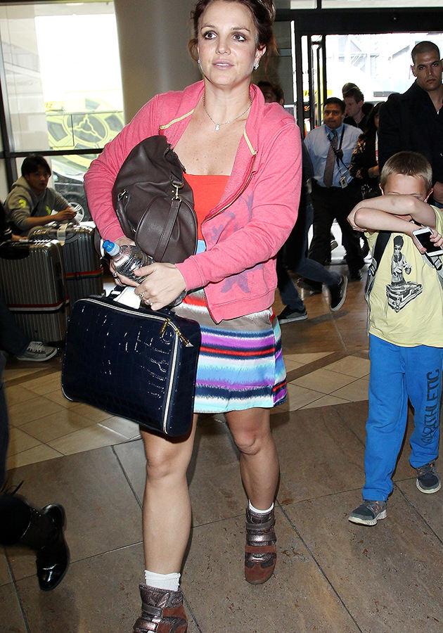 Бритни Спирс выглядела особенно потрепанной в розовом жилете поверх красной майки и в полосатой мини-юбке в аэропорту Лос Анджелоса.