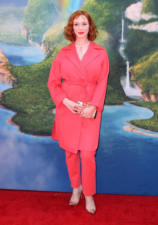 Christina Hendricks. Когда бэкграунд нельзя взять с собой. А так совсем не плохо розовый брючный костюм на фоне фотообоев.