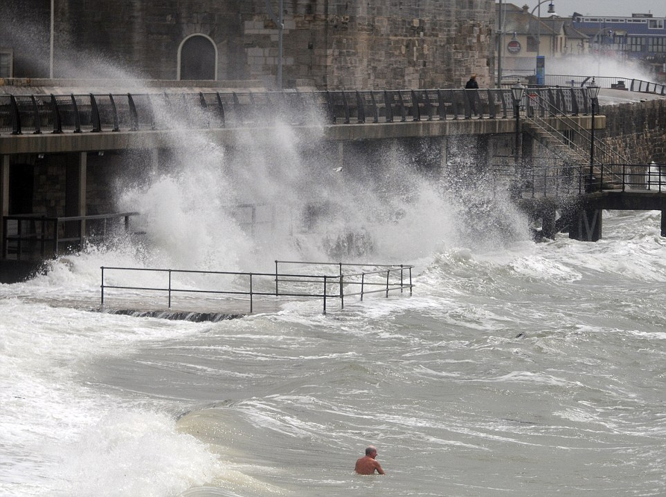 As gales and high winds of up to 70mph lashed the English coast, most swimmers kept well away from the beaches, except for two intrepid veterans who refused to let the storm-force conditions get in the way of their daily dip. Waves crashed against the ancient battlements of the Hot Walls in Old Portsmouth but even at 30 feet, were apparently not big or high enough to deter these brave swimmers, members of a group who strip off and jump in every day of the year whatever the weather. Coastguards were on alert for small boats in distress and the nearby hovercraft service from Southsea to Ryde, Isle of Wight was suspended. But these two men defied the conditions, the south-westerly gales and sea temperatures of just eight degrees Celsius to spend 20 minutes splashing around as the huge waves swept past them before smashing against the walls behind. They both emerged unscathed, dressed after drying on the beach and then drove off, all the better for their blood-tingling and dangerous escapade. Ends Pic Mike Walker, Mike Walker Pictures
