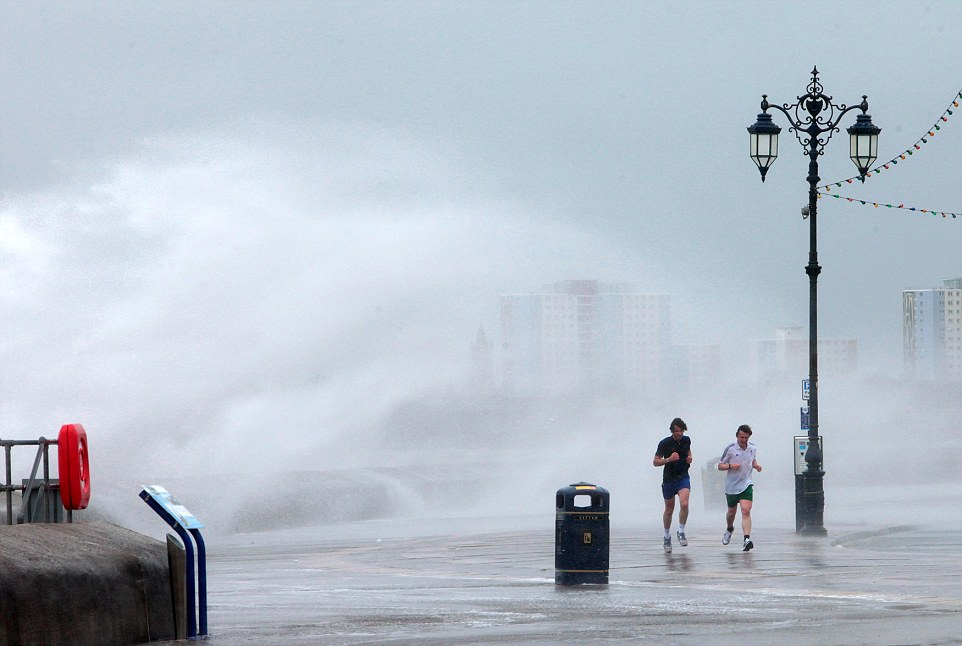 M and Y News Agency Ltd 06/05/15: Joggers run through waves breaking over the Southsea seafront, Portsmouth, Hants as high winds continued along the south coast throughout the day. Matt Scott-Joynt Photographer  M and Y News Agency Ltd Portsmouth Hampshire 02392820311 07853233144
